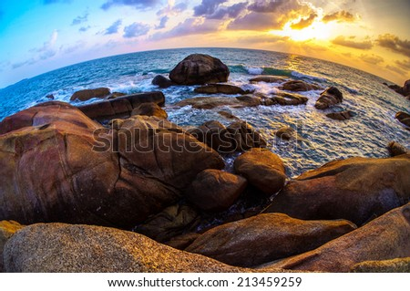 Fish-eye view of bi-color sunset on Samui island boulder shoreline, Thailand.  - stock photo