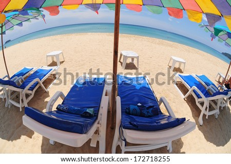 Fish eye view of white sand beach with chairs, colorful umbrella, and blue sky, Phuket, Thailand - stock photo
