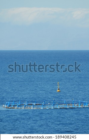 Fish Farm in the Atlantic Ocean on a Blue Day - stock photo