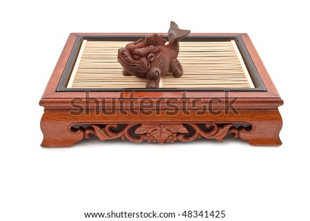 fish figurine on chinese wooden table isolated on white