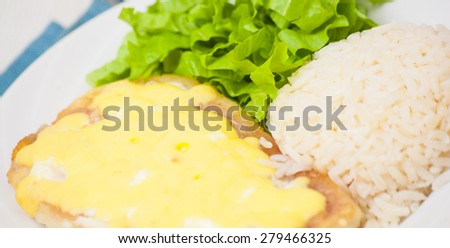 fish fillet under cheese with rice and salad - stock photo