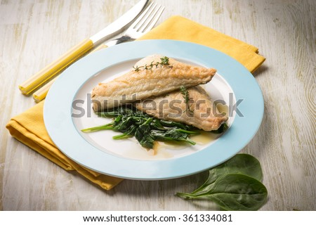 fish fillet with fresh spinach - stock photo