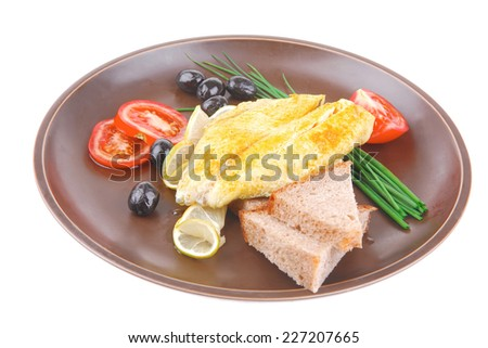 fish fillet with greek olives,tomatoes,chives and lemon on plate . shallow dof - stock photo
