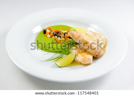 Fish fillet with sauce and vegetables on a plate - stock photo