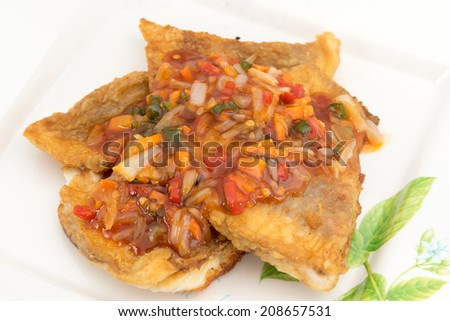 Fish Fillet with three flavor spicy sauce contains garlic, chili sauce, mushrooms, white onions, bell pepper, basil leafs