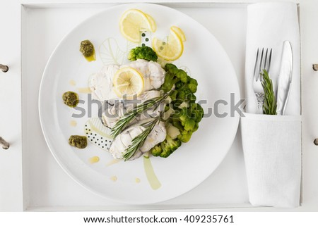 Fish fillet with vegetables and lemon and rosemary on white plate. Top wiew - stock photo