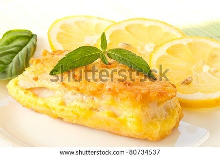 Fish fillets fried in batter with lemon and basil on a plate - stock photo
