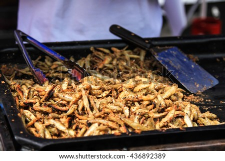 fish fried in oil anchovies in the street, fast food - stock photo
