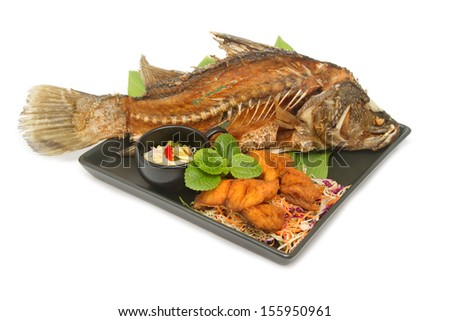 Fish fried with spicy mango salad in the black plate - stock photo