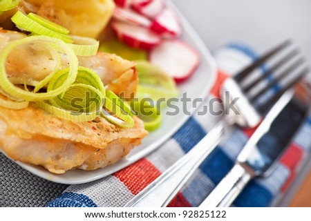 Fish in batter to plate on grey table. - stock photo