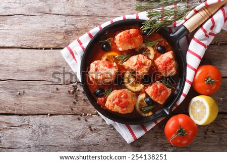 Fish in tomato sauce with olives and lemon in a frying pan. horizontal view from above  - stock photo