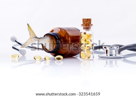 Fish liver oil capsules in bottle with stethoscope isolate on white background. - stock photo