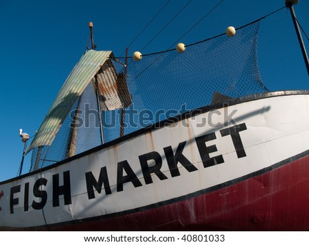 Fish Market sign on old fishing boat - stock photo