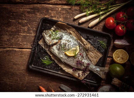 Fish Meat on a Black Tray with Herbs and Spices on Top of a Rustic Wooden Table with Organic Veggies. Captured in High Angle View. - stock photo