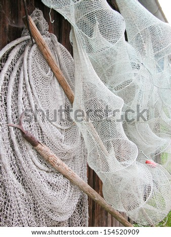 Fish Nets and Pike Poles Hanging on a Hut Wall - stock photo
