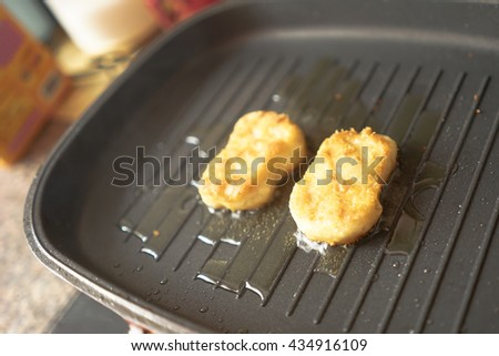 Fish nugget in hot cooking oil - stock photo