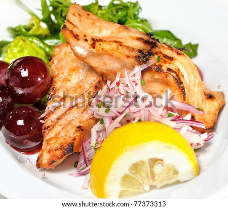 fish of grilled salmon, lettuce and lemon,grapes