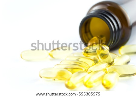 Fish oil capsules in a glass bottle on white background, healthy Vitamin supplementation concept,close up shot.