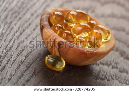 fish oil capsules in wooden bowl on table, health supplement - stock photo