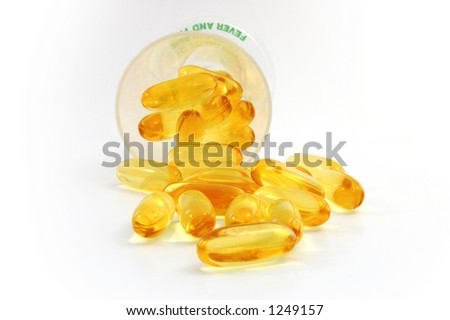 fish oil +evening primrose oil caplets spilling out from the cup . - stock photo