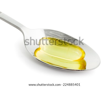Fish oil in spoon on a white background, close-up - stock photo