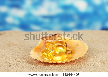 fish oil in the shell in the sand on a blue background - stock photo