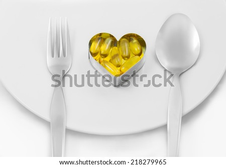 Fish Oil On Heart as Main menu between fork and spoon ion white dish solated on white background - stock photo