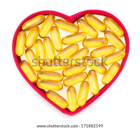 Fish oil pills in red heart shaped box isolated on white background  - stock photo