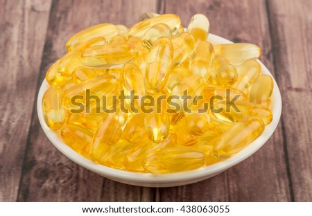 Fish oil supplement capsule in white bowl over white background