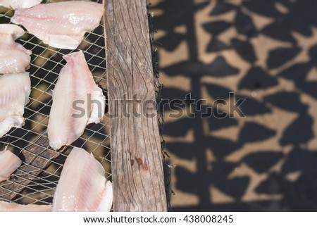 Fish on a grill to dry by the sun for preservation. Selective Focus. - stock photo