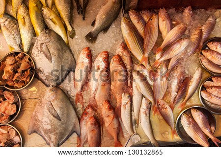 Fish on ice at a market stall - stock photo