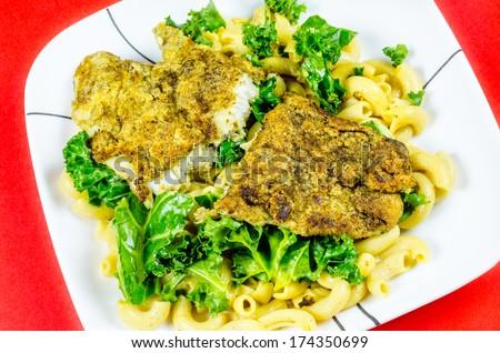 Fish on top on kale & gluten free pasta - stock photo