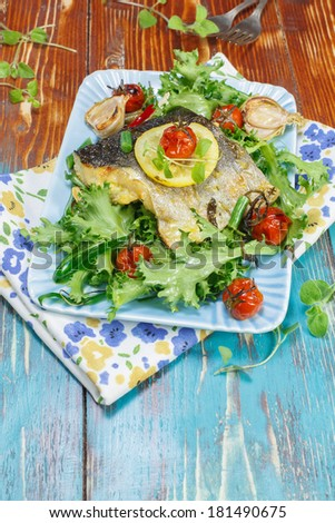 Fish. Roast Cod  on plate with lemon, garlic and vegetables - stock photo