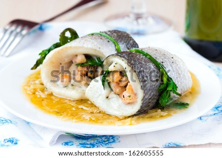 Fish rolls of dorado fillet stuffed shrimp and spinach with onion sauce of leek and wine - stock photo