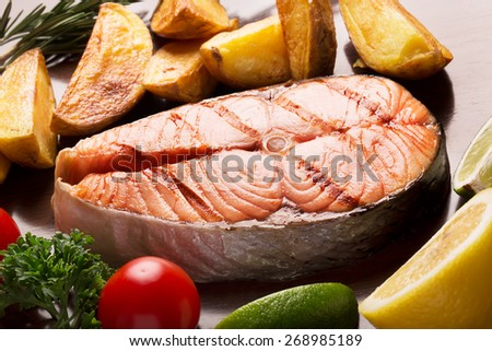 Fish (salmon) and fried potato chips with herbs
