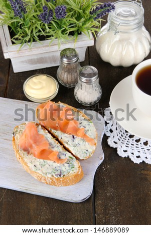 Fish sandwiches and cup of tea on cutting board on wooden table