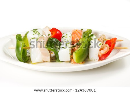 fish skewers  on a white table with oil and wine