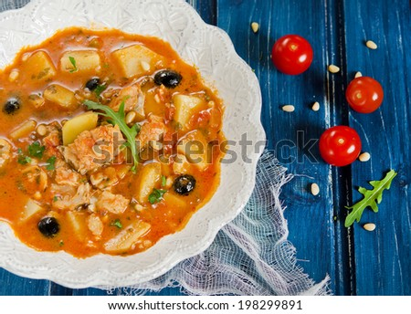 Fish soup with cod, potatoes, tomatoes and black olives - stock photo