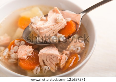 fish soup with salmon and orge perl���© in spoon on bowl - stock photo