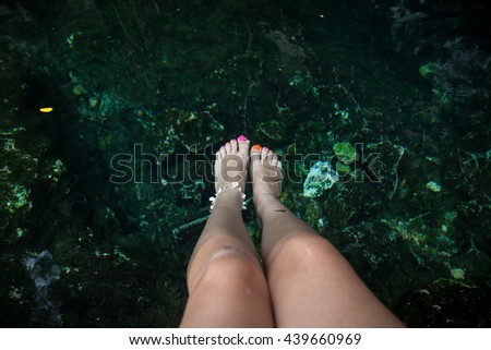 Fish spa therapy with female legs in mexican cenotes