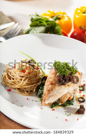 fish steak, decorated fish steak with pan fried spinach side with spaghetti on dish - stock photo