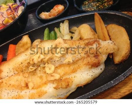 Fish steak on hot plate - stock photo