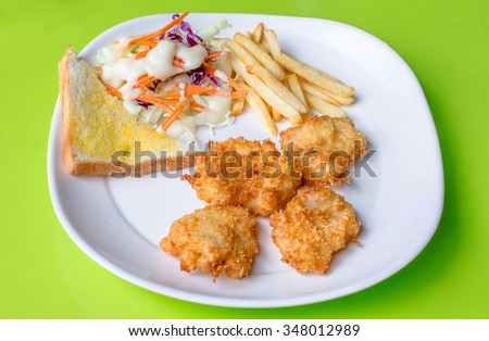 Fish Steaks, french fries with vegetables salad on a plate