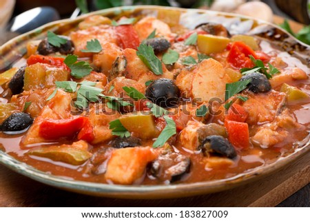 fish stew in tomato sauce on a plate, close-up, horizontal