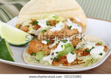 Fish tacos on tortilla shell with lime slices - stock photo