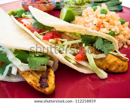 Fish Tacos with Guacamole and Rice: Seasoned grilled fish tacos in corn tortillas with salsa, cabbage, guacamole, lime, and rice. - stock photo