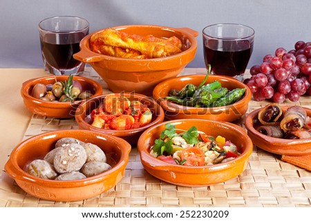 Fish tapas foods in terracotta bowls, appetizers including dates in bacon, seafood salad, chicken in tomato sauce and pickled olives, salty potatoes, chorizo and pepperoni, red wine and grapes. - stock photo