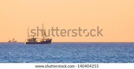 Fish trawler on the distance against a clear dusk sky over the North Sea - stock photo