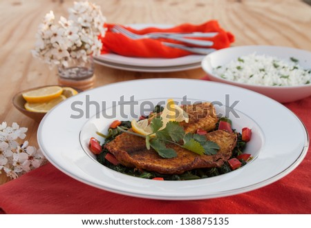 Fish with sauteed spinach - stock photo