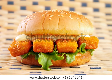 Fishburger with fish sticks and mayonnaise on table mat - stock photo